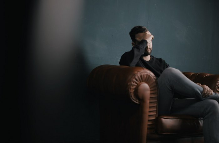 Reduce Migraine Symptoms - man sitting quietly holding his head with migraine