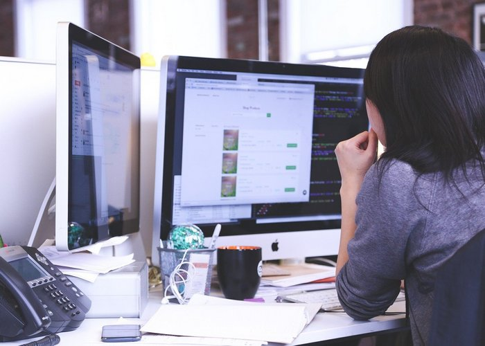 Girl working at a desk designing a website - article header for - How Web Design and SEO Go Together